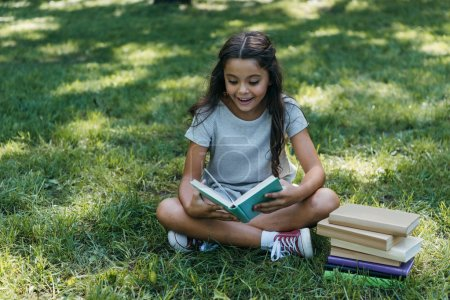Photo for Adorable happy child sitting on grass and reading book in park - Royalty Free Image