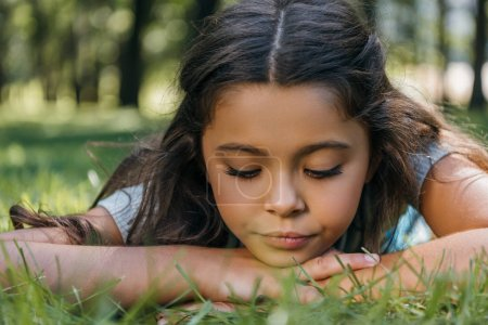 close-up view of adorable child lying on grass and looking down in park