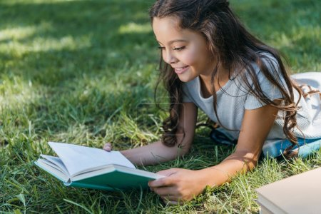 cute smiling child lying on grass and reading book