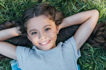 Photo for Beautiful happy child lying with hands behind head on grass and smiling at camera - Royalty Free Image