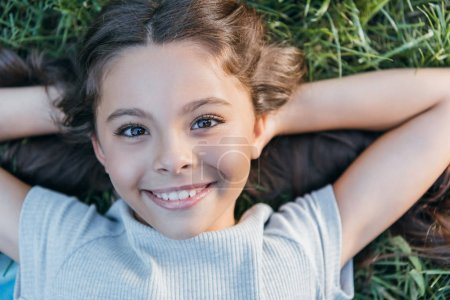 Photo for Top view of happy child lying with hands behind head on grass and smiling at camera - Royalty Free Image