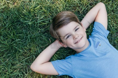 Photo for Top view of happy boy lying with hands behind head on grass and smiling at camera - Royalty Free Image