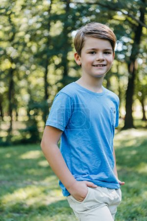 Photo for Portrait of adorable child standing with hands in pockets and smiling at camera in park - Royalty Free Image