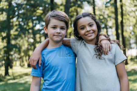 Photo for Beautiful happy kids hugging and smiling at camera in park - Royalty Free Image