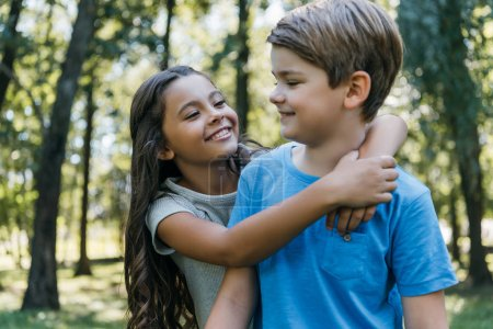 Photo for Cute happy children hugging and smiling in park - Royalty Free Image