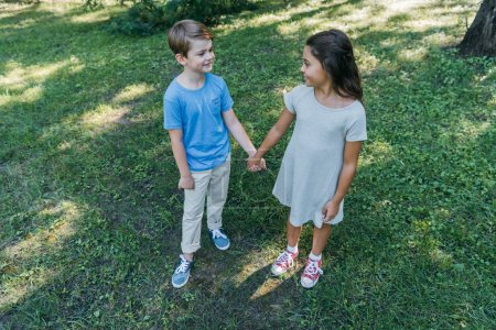high angle view of cute children holding hands and smiling each other in park