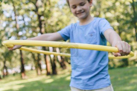 Foto de Recortar foto de adorable niño feliz jugando con el hula hoop en Parque de - Imagen libre de derechos