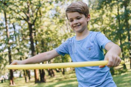 Foto de Lindo niño feliz jugando con el hula hoop en Parque de - Imagen libre de derechos