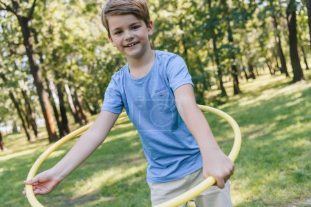 Foto de Niño feliz jugando con el aro del hula y sonriendo a la cámara en el Parque - Imagen libre de derechos
