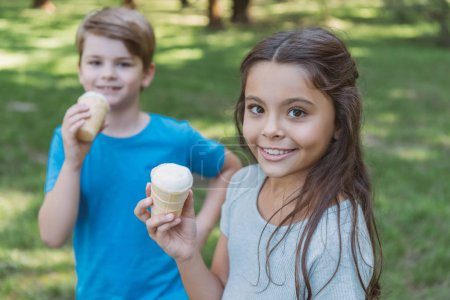 adorable happy kids eating ice cream and looking at camera in park
