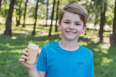 cute happy boy holding ice cream and smiling at camera in park