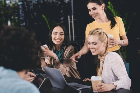 Foto de Sonriendo empresaria señalando en la pantalla del ordenador portátil a dos empresarias en oficina moderna - Imagen libre de derechos
