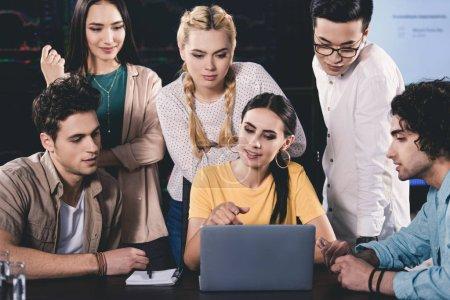 jeune femme d'affaires, pointant sur l'écran du portable à ses collègues de bureau moderne