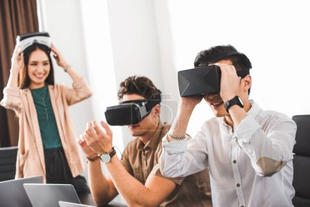 two smiling businessmen using virtual reality headsets at modern office