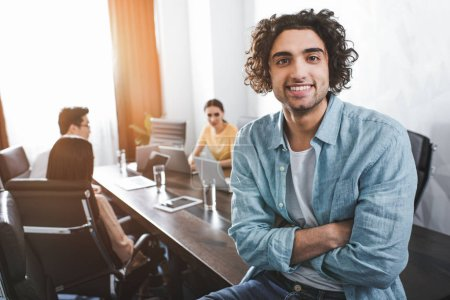smiling young businessman with crossed hands looking at camera and his partners working behind at modern office