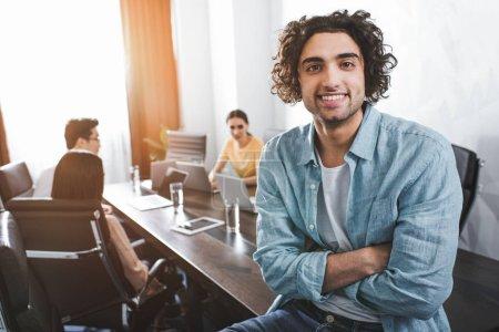 Photo pour Jeune homme d'affaires souriant avec les mains croisées regardant la caméra et ses partenaires travaillant derrière au bureau moderne - image libre de droit