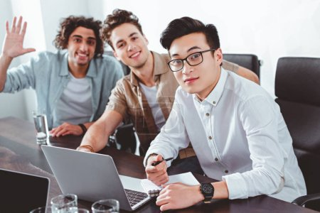 three multicultural businessmen at table with laptops in modern office