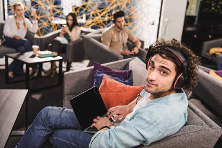 Photo for Young businessman in headphones sitting on couch and using laptop with blank screen at modern coworking office - Royalty Free Image