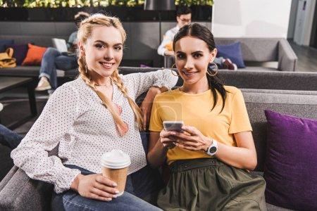 Photo pour Deux femmes d'affaires souriants avec café et smartphone au bureau de coworking moderne - image libre de droit