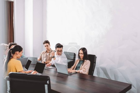 partenaires d'affaires multiculturelles ayant séance à table avec les ordinateurs portables au bureau moderne
