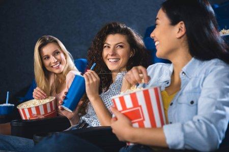 Photo pour Heureuse femme multiraciale avec pop-corn en regardant le film ensemble dans la salle de cinéma - image libre de droit
