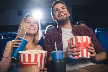 happy couple with popcorn watching film together in cinema