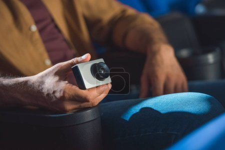 partial view of man with small video camera illegally filming movie in cinema