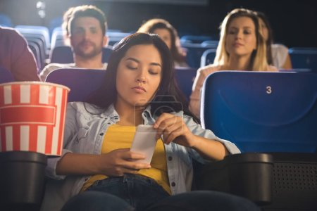 asian woman using smartphone while watching movie in cinema