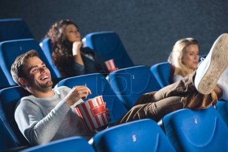 Photo for Cheerful man with popcorn laughing while watching film in cinema - Royalty Free Image