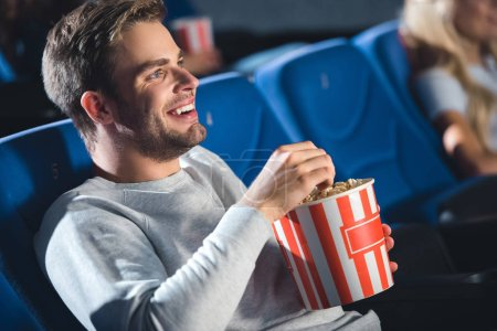 side view of cheerful man with popcorn watching film in cinema
