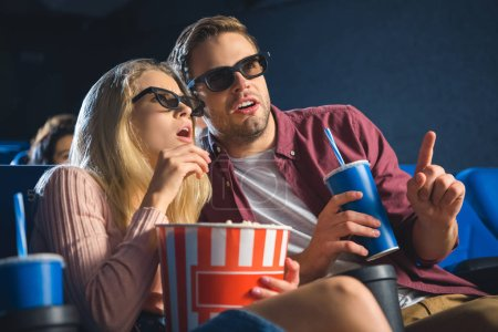 emotional couple in 3d glasses with popcorn watching film together in cinema