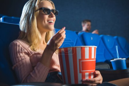 smiling woman in 3d glasses with popcorn watching film alone in cinema
