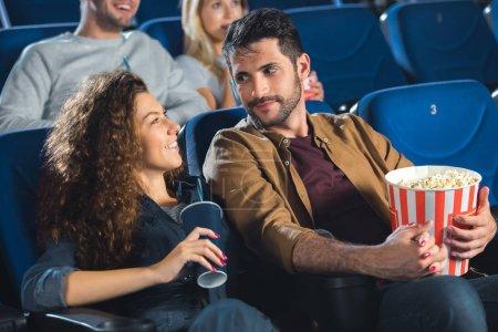 Photo pour Couple avec pop-corn en regardant le film ensemble au cinéma - image libre de droit