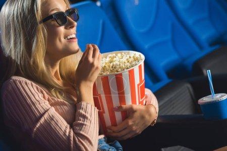 Foto de Vista lateral de la sonriente mujer de gafas 3d con palomitas de maíz viendo la película sola en cine - Imagen libre de derechos