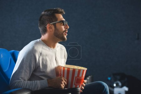 side view of emotional man in 3d glasses with popcorn watching film alone in cinema