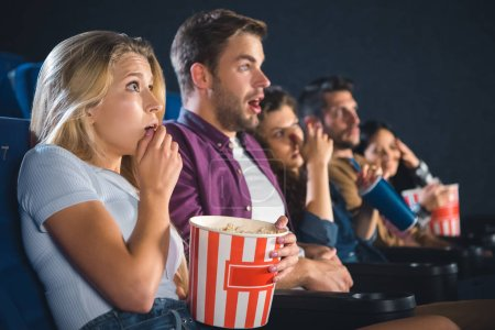 scared multiethnic friends with popcorn watching film together in movie theater