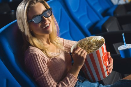 young woman in 3d glasses with popcorn watching film alone in cinema