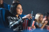 side view of smiling asian woman with popcorn and soda drink watching movie in cinema