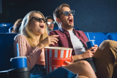 shocked couple in 3d glasses with popcorn watching film together in cinema