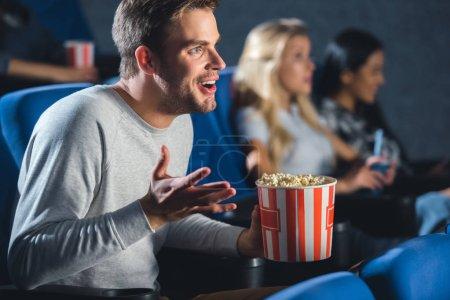 Photo pour Mise au point sélective d'homme émotif avec pop-corn au cinéma - image libre de droit