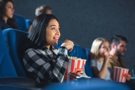 Photo for Emotional asian woman with popcorn watching movie in cinema - Royalty Free Image