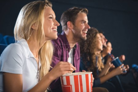 Photo for Cheerful friends with popcorn watching film together in movie theater - Royalty Free Image