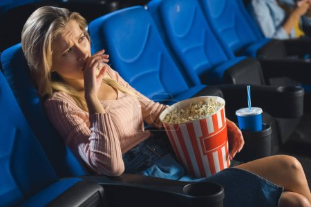 young emotional woman with popcorn watching film alone in cinema