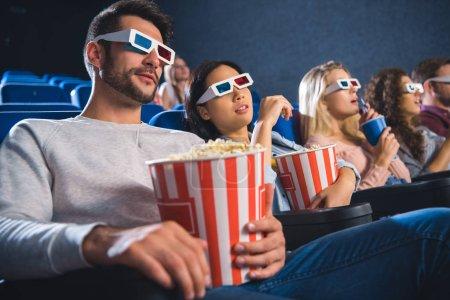 Photo pour Amis multiethniques dans lunettes 3d avec pop-corn en regardant le film ensemble dans la salle de cinéma - image libre de droit
