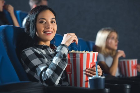 smiling asian woman with popcorn looking at camera in cinema