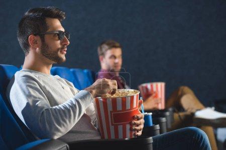 Photo pour Mise au point sélective de l'homme dans les lunettes 3d avec pop-corn je regarde le film en salle de cinéma - image libre de droit
