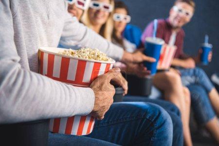 Photo pour Vue partielle des amis multiethniques avec pop-corn en regardant le film ensemble dans la salle de cinéma - image libre de droit