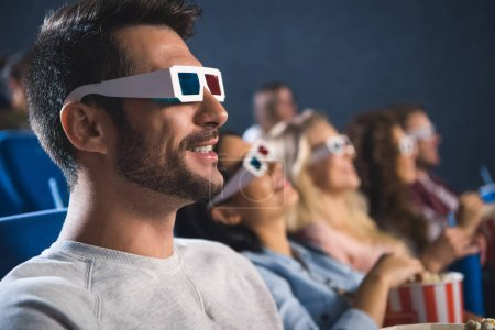 Photo for Selective focus of multiethnic friends in 3d glasses with popcorn watching film together in movie theater - Royalty Free Image