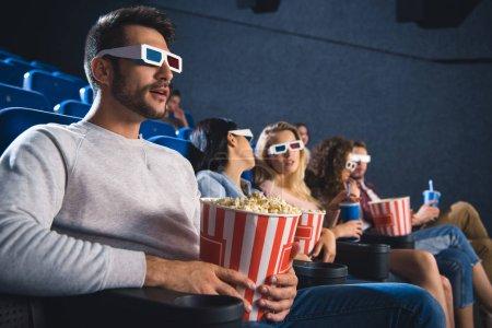 Photo pour Mise au point sélective des amis multiethniques dans lunettes 3d avec pop-corn en regardant le film ensemble dans la salle de cinéma - image libre de droit
