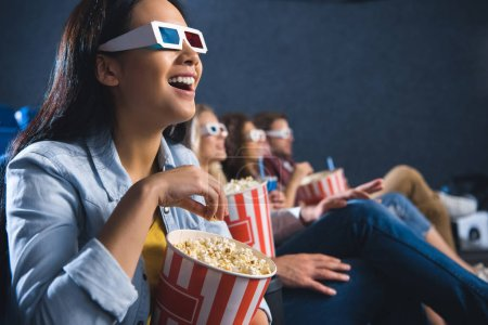happy asian woman in 3d glasses with popcorn watching movie in cinema